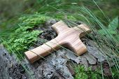 Wooden cross with tree on a green natural background