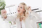 Blond woman is sitting in office with happy face