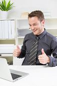 Laughing businessman showing alright with thumb