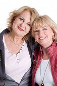 Two Caucasian senior women smiling at the camera.