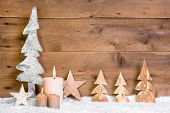 Christmas decoration:wooden trees,stars,candles and snow on wooden background