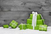 Stack of green Christmas presents, with snow on grey wooden background