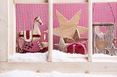 Indoor window sill Christmas decoration: rocking horses,stars, lantern and snow