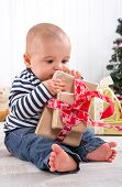 First Christmas: baby unwrapping present