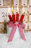 Four burning candles in front of a advent calendar - greeting card for christmas
