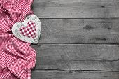 Wooden background for a greeting card or a voucher with a red chequered heart for christmas, mother's day, valentine's day, birthday or wedding or to say thank you