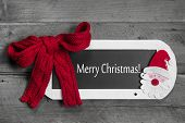 Red bow on menu board with Merry Christmas message on wooden background