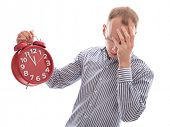 Eleventh hour - stressed man holding clock hiding behind hand isolated on white background