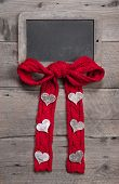 Chalkboard for message with red knitted bow and hearts on grey wooden background for valentine's day, mother's day, birthday or anniversary