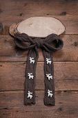 Wooden sign with brown bow and reindeer or elk on wooden background