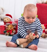 First Christmas: baby unwrapping a present - playing with a plush animal