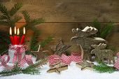 Christmas card with wooden stars, ribbon, pine branch, snow and four red burning candles and moose on wooden background