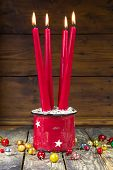 Four red christmas candles on a wooden background with old christmas balls - vintage or country style