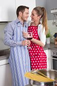 Couple in love cooking together in the kitchen and have fun - drinking red wine