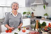 Senior or older woman with grey hair cooking in kitchen - vegetables