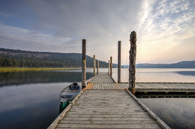stock photo of dock a lake  - The morning light on the dock with a canoe by it on Chatcolet Lake near Plummer Idaho - JPG