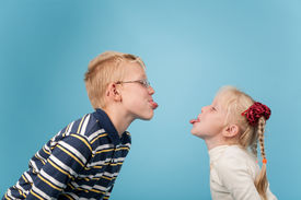 image of sticking out tongue  - Teenage boy and girl stick out tongues to each other - JPG