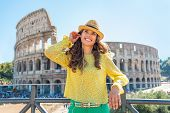 Happy Young Woman With Audio Guide In Front Of Colosseum In Rome, Italy