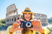 Happy Young Woman Taking Photo In Front Of Colosseum In Rome, It