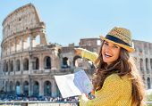 Happy Young Woman With Map Pointing On Colosseum In Rome, Italy