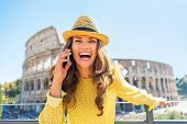 Smiling Young Woman Talking Cell Phone In Front Of Colosseum In