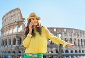Young Woman Talking Cell Phone In Front Of Colosseum In Rome, It