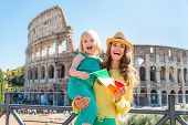 stock photo of italian flag  - Happy mother and baby girl with italian flag in front of colosseum in rome italy - JPG