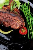 savory plate: grilled ribs over black with peppers and green salad