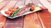 whole fried bass on plate over wood, served with lemons and tomatoes