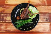 savory on black: grilled ribs on plate over wooden table