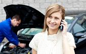 Man Repairing Car Of Busy Woman