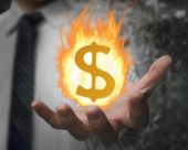 Burning Fire Ball Of Dollar Sign In Businessman's Hand