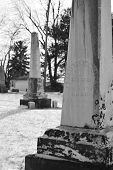 picture of tombstone  - Two obelisk tombstones are seen in black and white in winter - JPG