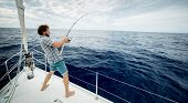 Young man fishing in open sea from sail boat