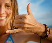 Happy smiling lady surfer showing shaka sigh. Focus on the hand