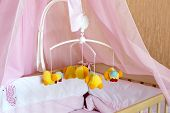 Toy Carousel On The Cot With Orange Linen