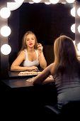 Blonde Woman Applying Makeup At Vintage Theater Mirror