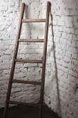 Old Wooden Ladder Leaning Against White Brick Wall