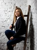 Sexy Blonde Woman In Jacket Sitting On Wooden Ladder At Studio
