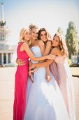 foto of friendship day  - Portrait of beautiful bride hugging with bridesmaids at sunny day - JPG