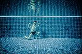 Man posing as Superman underwater swimming pool