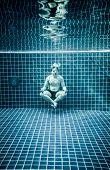 Man under water in a swimming pool to relax in the lotus position