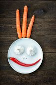 Smiley face made from pepper, garlic,flavoring and carrots