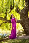 picture of mystique  - Full length portrait of sexy woman in long dress leaning against big tree at riverbank - JPG