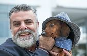 Attractive Old Man With Beard And Hat With Dog