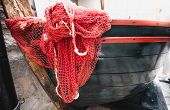 foto of fishnet  - Closeup shot of red fishnet lying blue wooden rowboat - JPG