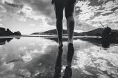 picture of wet feet  - Black and white photo of female legs walking on water with sky reflecting on it - JPG