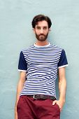 Cool Male Model In Striped Shirt Leaning Against Wall