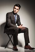 Full body image of a young elegant business man sitting on a stool againt studio backgroud, looking to his side while holding his hands together.