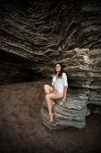 foto of cave woman  - Beautiful slim woman sitting on big cliff at sea cave - JPG